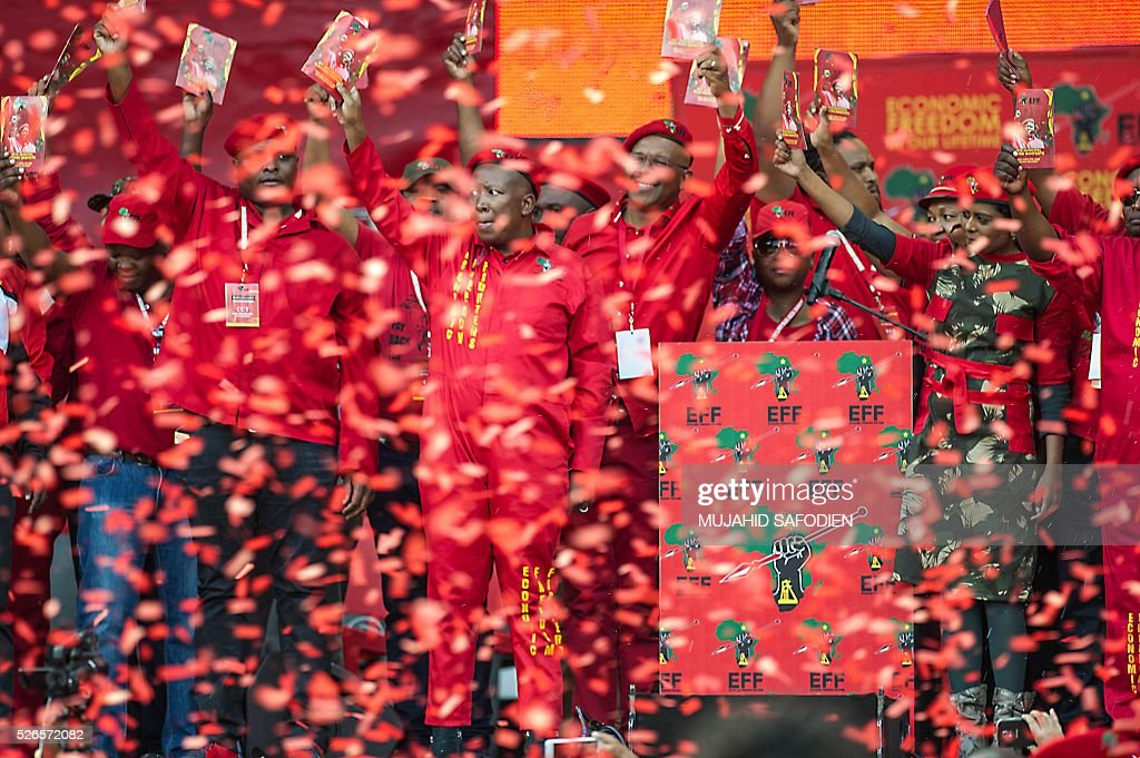 Economic Freedom Fighters leader Julius Malema (C) and EFF leadership hold a pamphlet with their political manifesto during the EFF official local election manifesto launch at Soweto's Orlando Stadium in Johannesburg on April 30, 2016. Around 40,000 people turned Orlando stadium in Soweto into a sea of red as supporters roared their approval of fiery EFF leader Julius Malema's promises to seize white-owned land without compensation and nationalise the banks, targeting white privilege and the ruling African National Congress. / AFP / MUJAHID