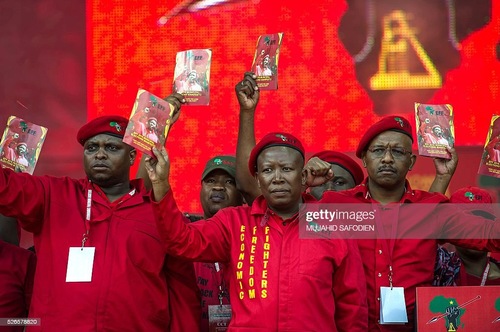 South African opposition radical party Economic Freedom Fighters leader Julius Malema (C) and EFF leadership hold a pamphlet with their political manifesto during the EFF official local election manifesto launch at Soweto's Orlando Stadium in Johannesburg on April 30, 2016. Around 40,000 people turned Orlando stadium in Soweto into a sea of red as supporters roared their approval of fiery EFF leader Julius Malema's promises to seize white-owned land without compensation and nationalise the banks, targeting white privilege and the ruling African National Congress. / AFP / MUJAHID