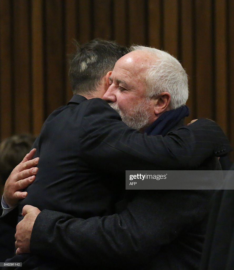 South African Paralympian Oscar Pistorius hugs his father Henke Pistorius on the third day of his hearing at the Pretoria High Court for sentencing...