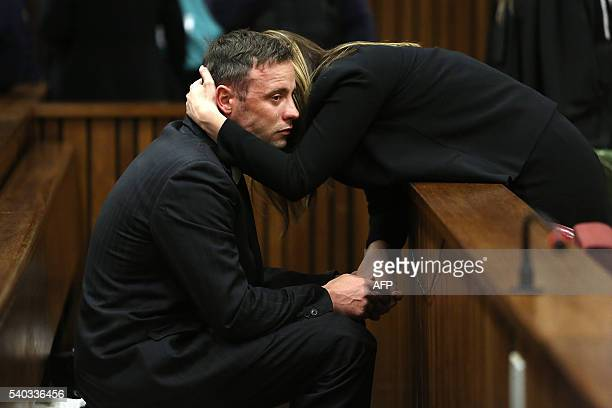 TOPSHOT South African Paralympian Oscar Pistorius reacts as his sister holds him during the third day of his resentencing hearing for the 2013 murder...