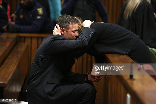 South African Paralympian Oscar Pistorius reacts as his sister holds him during the third day of his resentencing hearing for the 2013 murder of his...