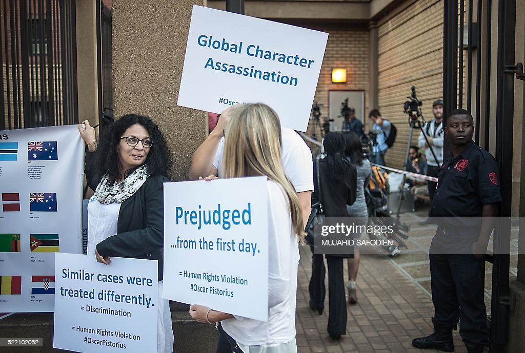 South African Paralympian Oscar Pistorius supporters hold banners as they protest outside the High Court for the postponement hearing in his murder case on April 18, 2016 in Pretoria. Disgraced South African athlete Oscar Pistorius's sentence for the murder of his girlfriend Reeva Steenkamp will be handed down in June, a judge said during a brief hearing on April 18, 2016. Pistorius's conviction for culpable homicide over Steenkamp's death in 2013 was upgraded to murder on appeal. / AFP / MUJAHID