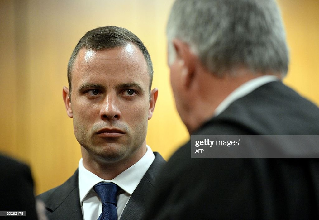 South African Paralympic athlete Oscar Pistorius talks with his lawyer Barry Roux during his ongoing murder trial on March 24, 2014 in Pretoria. Oscar Pistorius's murder trial entered its fourth week with more testimony on gunshots and a woman's terrified screams on the night the star Paralympian shot dead his glamorous girlfriend. AFP PHOTO / POOL Chris Collingridge