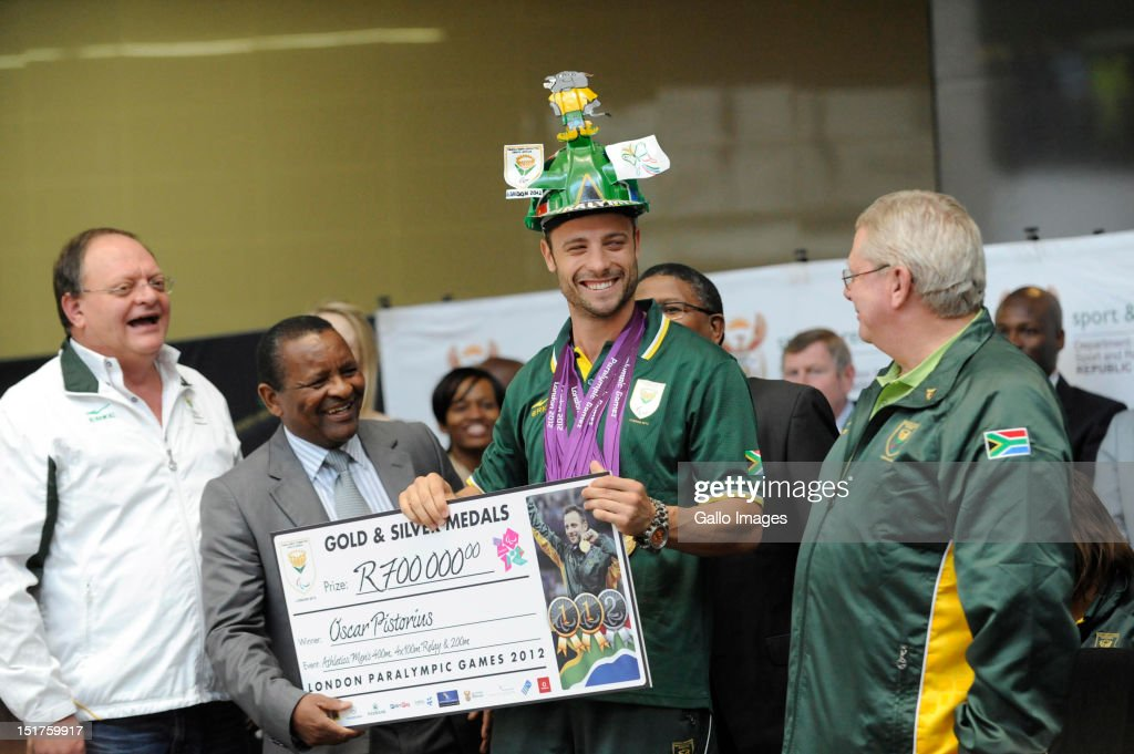 South African Paralympic Gold Medal winning sprinter <a gi-track='captionPersonalityLinkClicked' href=/galleries/search?phrase=Oscar+Pistorius&family=editorial&specificpeople=224406 ng-click='$event.stopPropagation()'>Oscar Pistorius</a> (2R) receives a cheque of R700,000 from Minister of Sports <a gi-track='captionPersonalityLinkClicked' href=/galleries/search?phrase=Fikile+Mbalula&family=editorial&specificpeople=4462961 ng-click='$event.stopPropagation()'>Fikile Mbalula</a> (2L) as Gert Oosthuizen (L) and Gideon Sam look on during the South African Paralympic team arrival at O.R Tambo International Airport on September 11, 2012 in Johannesburg, South Africa.