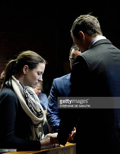 South African Paralympic sprinter Oscar Pistorius prays with his sister Aimee and his brother Carl as he appears at the Magistrate Court in Pretoria...