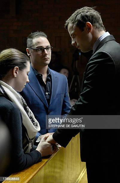 South African Paralympic sprinter Oscar Pistorius stands next to his sister Aimee and his brother Carl as he appears at the Magistrate Court in...