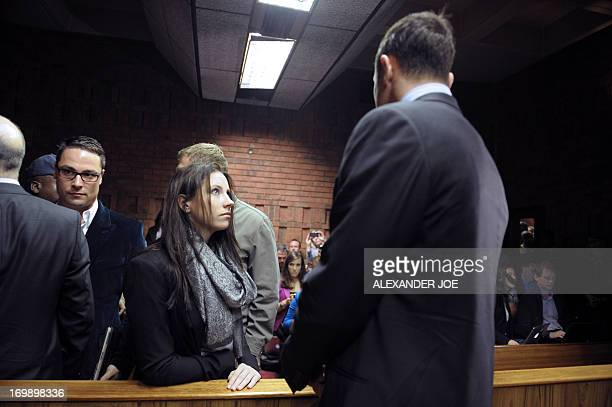 South African Paralympic sprinter Oscar Pistorius talks to his sister Aimee on June 4 2013 in the Magistrate Court in Pretoria after appearing for...
