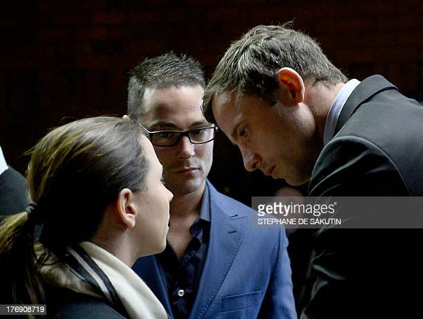 South African Paralympic sprinter Oscar Pistorius talks with his sister Aimee and his brother Carl as he appears at the Magistrate Court in Pretoria...