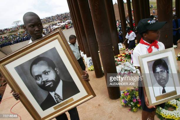 South African people hold a photo of late President Samora Machel and other victims of his plane crash 19 October 2006 in Mbuzni at a memorial built...