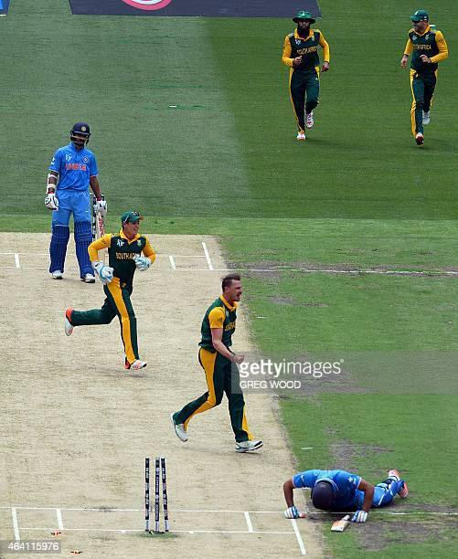 South African players Dale Steyn and Quinton de Kock AB de Villiers and Hashim Amla celebrate the runout of India's Rohit Sharma as India's Shikhar...
