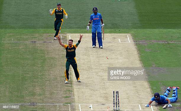 South African players Dale Steyn and Quinton de Kock celebrate the runout of India's Rohit Sharma as India's Shikhar Dhawan looks on during the Pool...