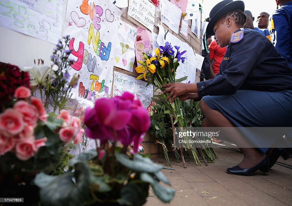 South African Police Academy trainees and instructors leave flowers for former South African President Nelson Mandela outside the Mediclinic Heart Hospital June 25, 2013 in Pretoria, South Africa. South African President Jacob Zuma confirmed Sunday that Mandela's condition has become critical since he was admitted to the hospital over two weeks ago for a recurring lung infection.