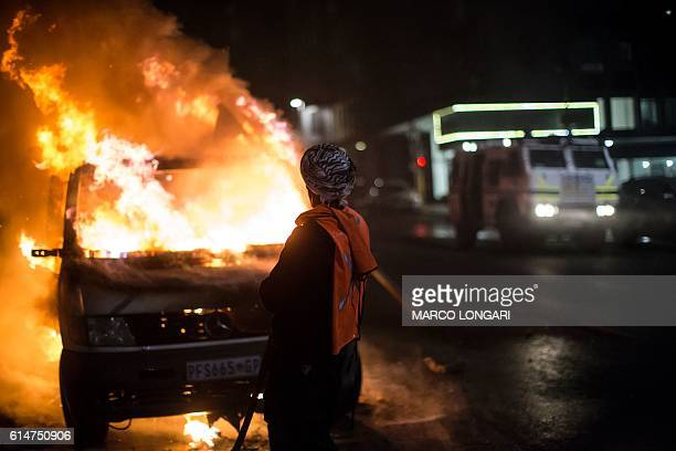 A South African police armoured personnel carrier is seen as a man douses a van on fire in front of the popular jazz bar 'the Orbit' in the...