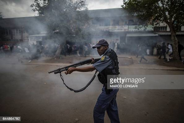 South African police forces aims his rifle during a stand off between members of the Somali community and anti immigrant demonstrators in the...