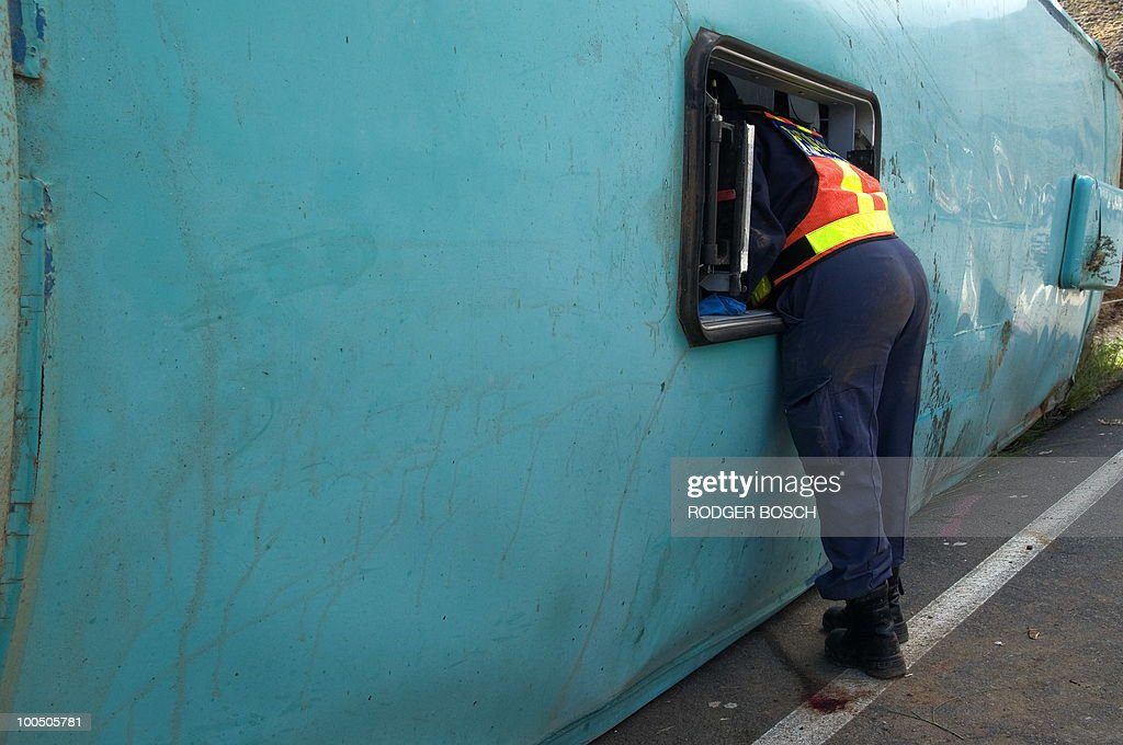 A South African police officer climbs through a roof emergency exit in the wreckage of a bus after its accident on the N1 on May 5, 2010 between De Doorns and Touws River some 150 kms north east of Cape Town. At least 24 people died and 15 were badly injured when an unroadworthy bus overturned in South Africa on May 5, raising concerns about transport ahead of next month's World Cup.