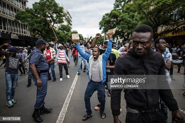 South African police officer tries to control a group of Nigerians as they faceoff with a group of South Africans during a standoff in the center of...