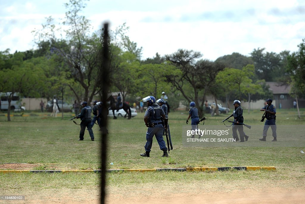 South African police officers advanced towards striking miners as rubber bullets, stun grenades and tear gas are used to disperse miners who were trying to prevent a rally organised by the Congress of South African Trade Unions (Cosatu) in Rustenburg, northwest of Johannesburg on October 27, 2012. Bullet casings littered the ground and a helicopter circled above, with police sirens howling, as the protesters were chased into the area surrounding the stadium. The clashes came a day after the National Union of Mineworkers (NUM) announced that it had reached a deal with the world's number one platinum producer Amplats to rehire 12,000 workers who were fired for a wildcat strike. Striking workers are disagree with the deal, which would signal a further winding down of a wave of wildcat strikes that have rocked platinum and gold mines since August.
