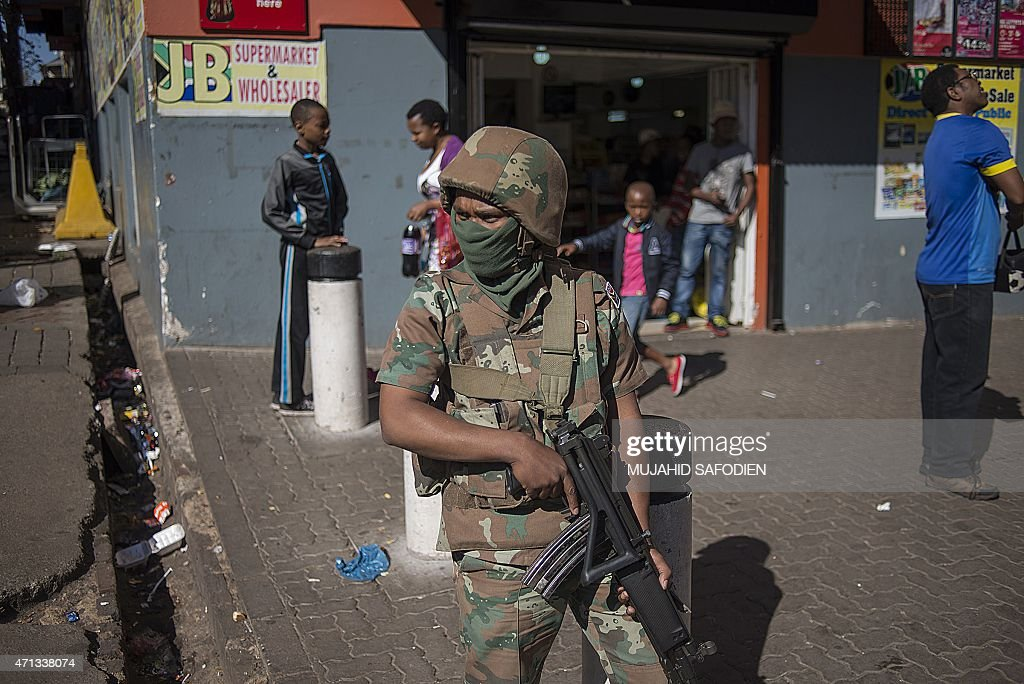 South African Police officers backed by soldiers of the South African Defence Force SADF conduct searches and identity checks in Hilbrow Johannesburg...