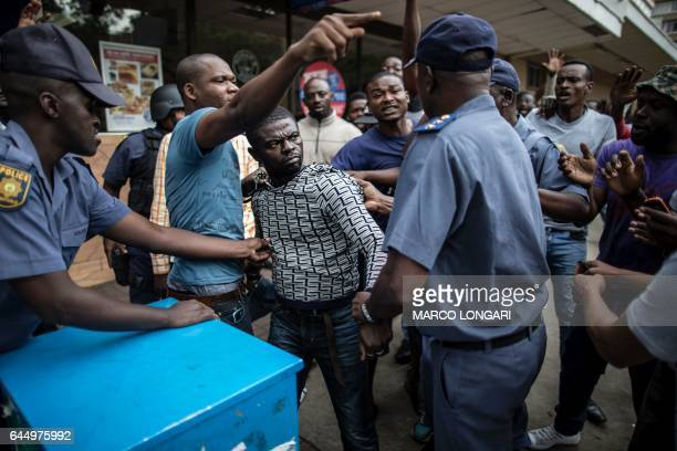 TOPSHOT South African police officers detain a Nigerian man during a faceoff with a group of South Africans in the center of Pretoria on February 24...