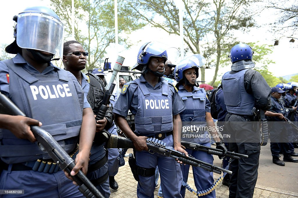 South African police officers face striking miners as rubber bullets, stun grenades and tear gas are used to disperse miners who were trying to prevent a rally organised by the Congress of South African Trade Unions (Cosatu) in Rustenburg, northwest of Johannesburg on October 27, 2012. Bullet casings littered the ground and a helicopter circled above, with police sirens howling, as the protesters were chased into the area surrounding the stadium. The clashes came a day after the National Union of Mineworkers (NUM) announced that it had reached a deal with the world's number one platinum producer Amplats to rehire 12,000 workers who were fired for a wildcat strike. Striking workers are disagree with the deal, which would signal a further winding down of a wave of wildcat strikes that have rocked platinum and gold mines since August.