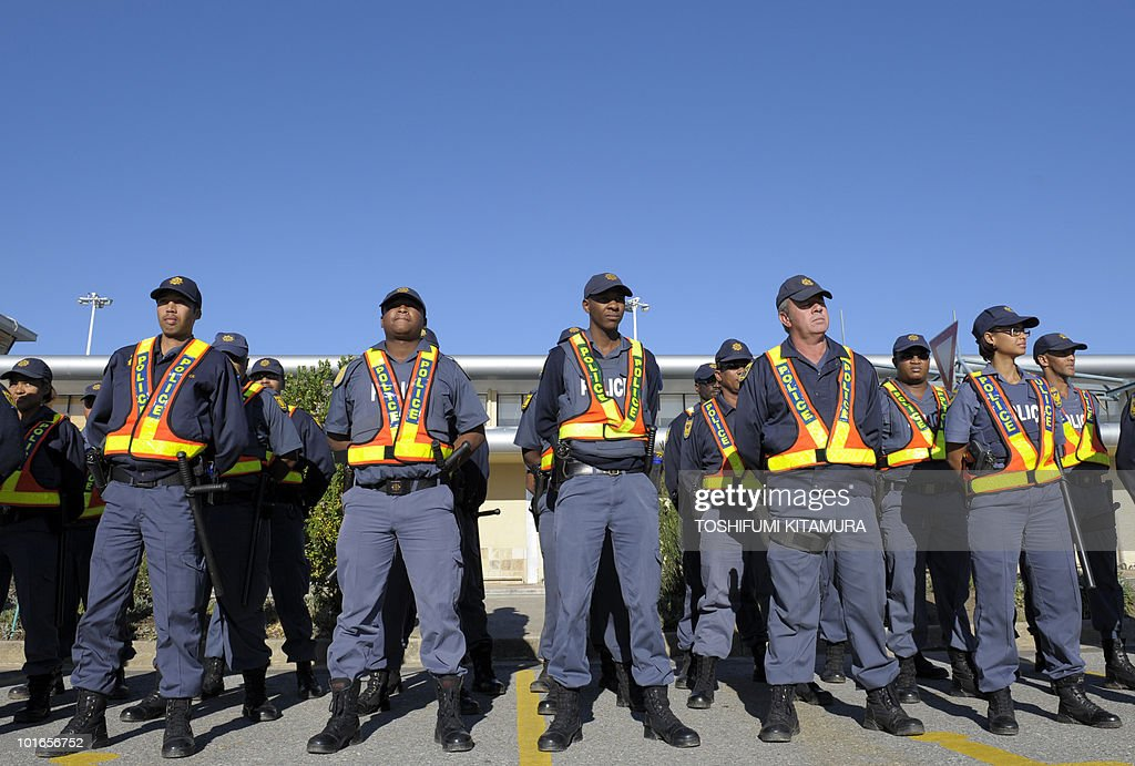 South African police officers stand at attention in front of the airport terminal waiting for the arrival of Japan's national football team in the South African city of George on June 6, 2010. The 2010 World Cup will take place in South Africa from June 11 to July 11, the first time on African soil for the biggest and most prestigious competition in sport.