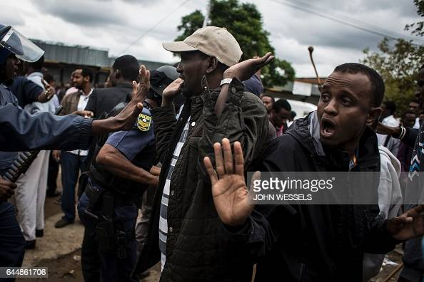 TOPSHOT South African police push away members from the Somalian community as the antiimmigrant march turns violent on February 24 2017 in Pretoria...
