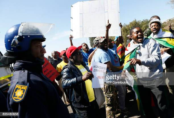 South African police stand guard as protesters from various Southern African Development Community countries demonstrate near the entrance to...