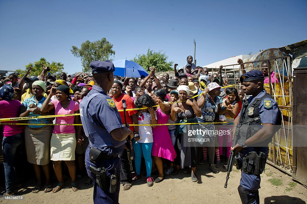 South African police stand guard as residents of Diepsloot township gather outside a crime scene, on October 15, 2013, after two toddlers were found dead inside a communal toilet in this slum north of Johannesburg, in another case of increasing brutal violence against children, police said. The bodies of the girls, aged two and three years, were discovered early in the morning by a resident.