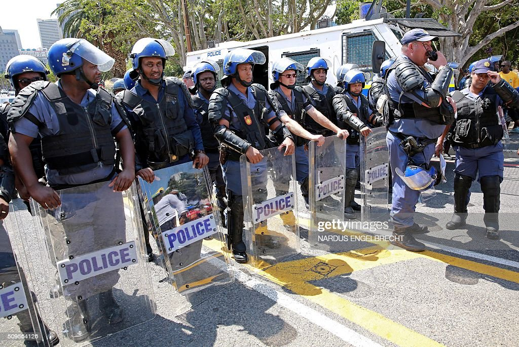South African Police stand in anti-riot gear as South African ruling party African National Congress and President Jacob Zuma supporters hold a demonstration in support of their president on February 11, 2016, in Cape Town, South Africa few hours ahead of his State of the Nation address. Police erected razor wire barricades outside the South African parliament on February 11 ahead of President Jacob Zuma's address to the nation against a background of concerted efforts to oust him from office. / AFP / NARDUS ENGELBRECHT