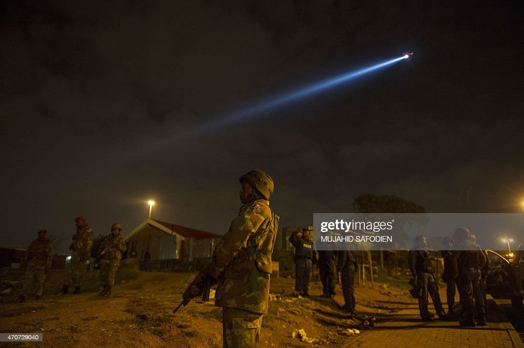 South African Police with the South African Defense Force SADF members look on during a raid on the Madoda Hostels in the Alexandra township of...