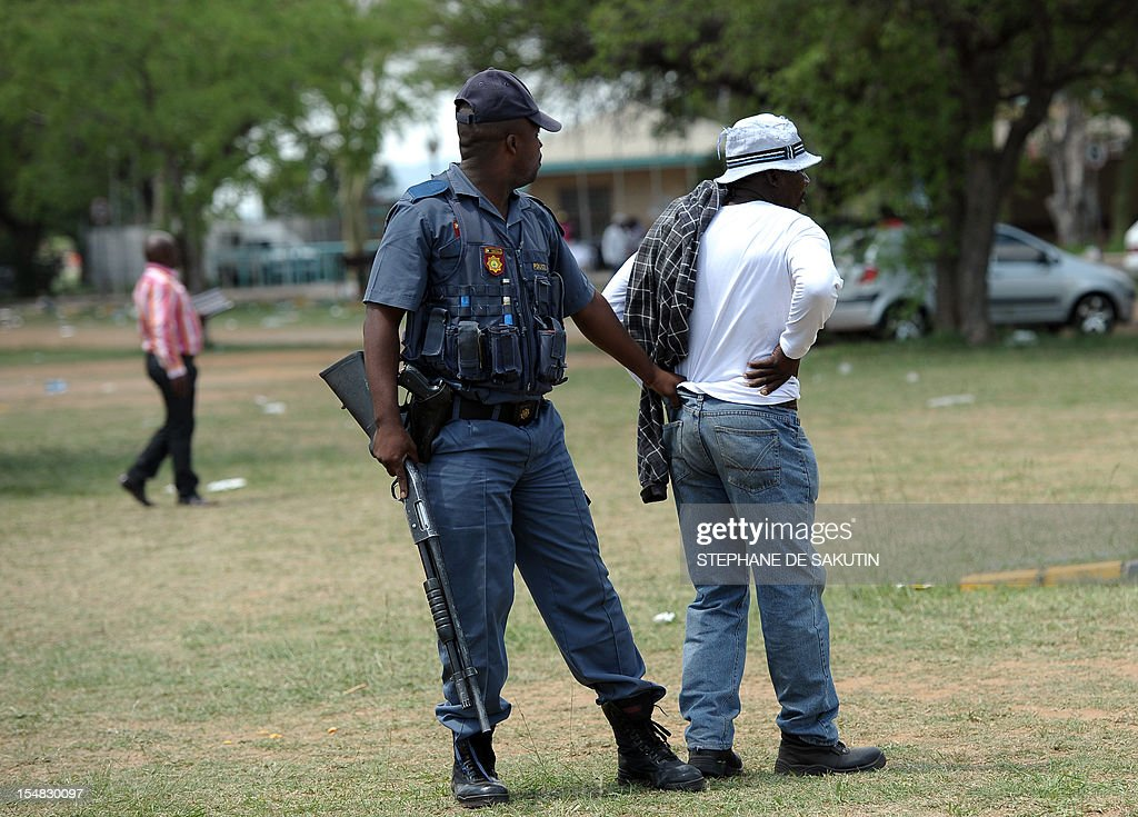 A South African policeman (L) arrests a striking miner as South African police officers fire rubber bullets, stun grenades and tear gas to disperse miners who were trying to prevent a rally organised by the Congress of South African Trade Unions (Cosatu) in Rustenburg, northwest of Johannesburg on October 27, 2012. Bullet casings littered the ground and a helicopter circled above, with police sirens howling, as the protesters were chased into the area surrounding the stadium. The clashes came a day after the National Union of Mineworkers (NUM) announced that it had reached a deal with the world's number one platinum producer Amplats to rehire 12,000 workers who were fired for a wildcat strike. Striking workers are disagree with the deal, which would signal a further winding down of a wave of wildcat strikes that have rocked platinum and gold mines since August. AFP PHOTO / STEPHANE DE SAKUTIN