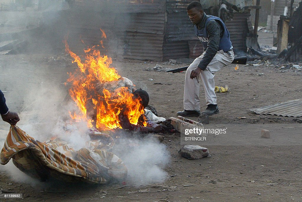 A South African policeman attends on May 18 2008 to a man that was set alight in Reiger Park during Xenophobic clashes that shook the whole of...