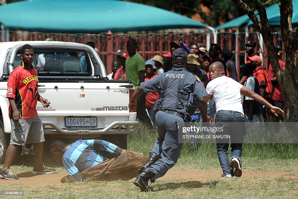 A South African policeman (2nd R) intervenes to protect a striking miner (2nd L) from being beaten by a member of the COSATU Union movement (R) as South African police officers fire rubber bullets, stun grenades and tear gas to disperse miners who were trying to prevent a rally organised by the Congress of South African Trade Unions (Cosatu) in Rustenburg, northwest of Johannesburg on October 27, 2012. Bullet casings littered the ground and a helicopter circled above, with police sirens howling, as the protesters were chased into the area surrounding the stadium. The clashes came a day after the National Union of Mineworkers (NUM) announced that it had reached a deal with the world's number one platinum producer Amplats to rehire 12,000 workers who were fired for a wildcat strike. Striking workers are disagree with the deal, which would signal a further winding down of a wave of wildcat strikes that have rocked platinum and gold mines since August.