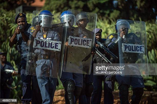 A South African policemen aim their rifle at protesters during clashes with students protesting against university fee hikes in front of the Union...