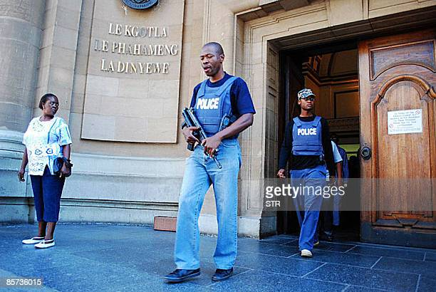 South African policemen walk at the exit of the South Gauteng High Court in Johannesburg on March 31 2009 following the attempted escape by two man...