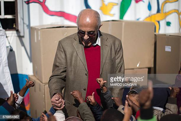 South African politician former political prisoner and antiapartheid activist Ahmed Kathrada salutes children as he takes part in a charity activity...