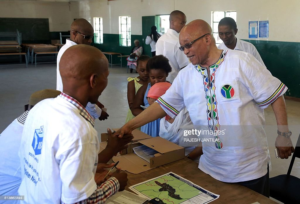South African president and leader of the ruling African National Congress party Jacob Zuma shake hands with Independent Electoral Commission...