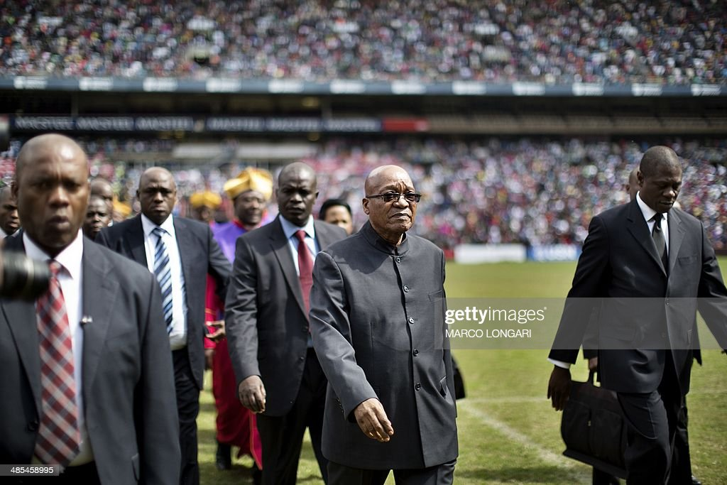 South African President Jacob Zuma acknowledges the crowd as he walks into Ellis Park stadium in Johannesburg to attend a Good Friday service with the Universal Church of the Kingdom of God.
