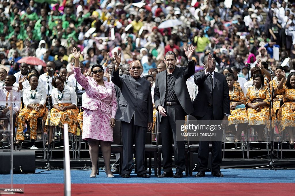 South African President Jacob Zuma (2nd L) acknowledges the crowd from the stage at the Ellis Park stadium in Johannesburg as he stands next to Bishop Marcelo Pires (2nd R) attending a Good Friday service with the Universal Church of the Kingdom of God on April 18, 2014.