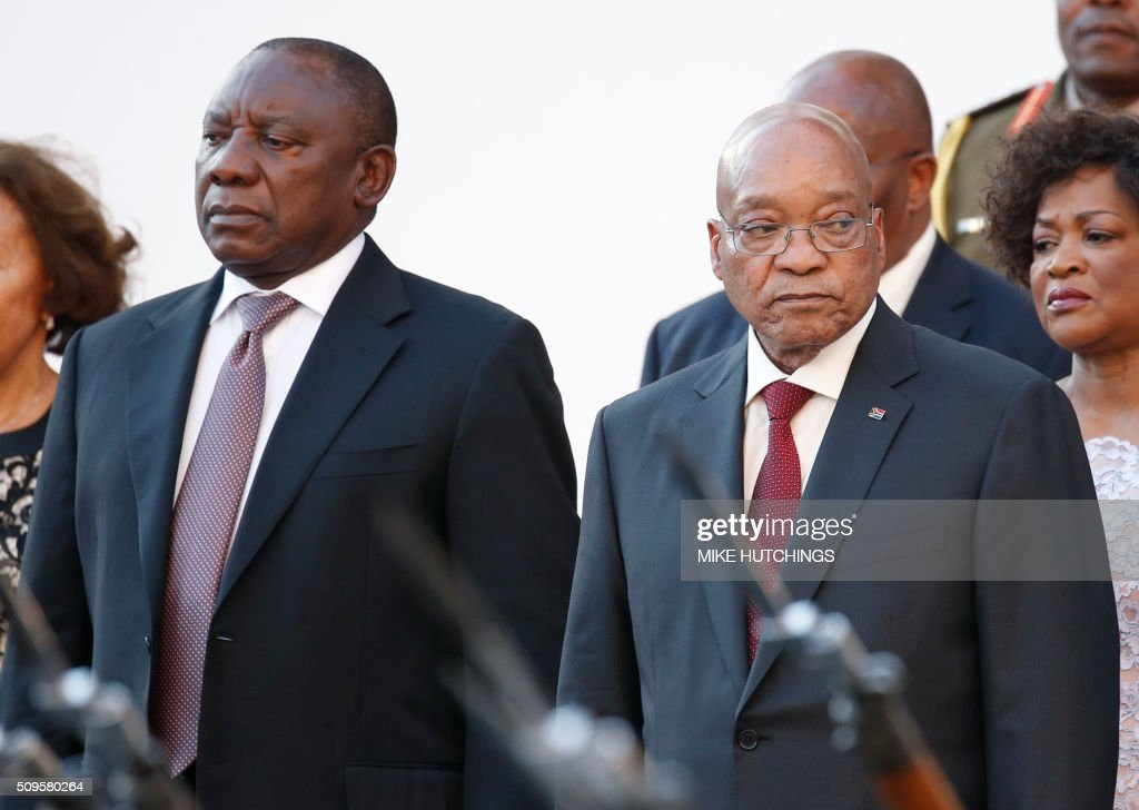 South African president Jacob Zuma (R) and South African deputy president Cyril Ramaphosa (L) stand for the National Anthem as they arrive for the President's State of the Nation Address on February 11, 2016 in Cape Town. South African President Jacob Zuma delivers his annual state of the nation address on February 11, 2016 as frustration grows over his leadership and the country's lack of progress since apartheid ended more than 20 years ago. Zuma's critics accuse him of allowing a small black elite to enrich itself, failing to help the poor, and overseeing national economic decline as South Africa struggles to overcome the legacy of decades of white-minority rule. / AFP / POOL / Mike HUTCHINGS