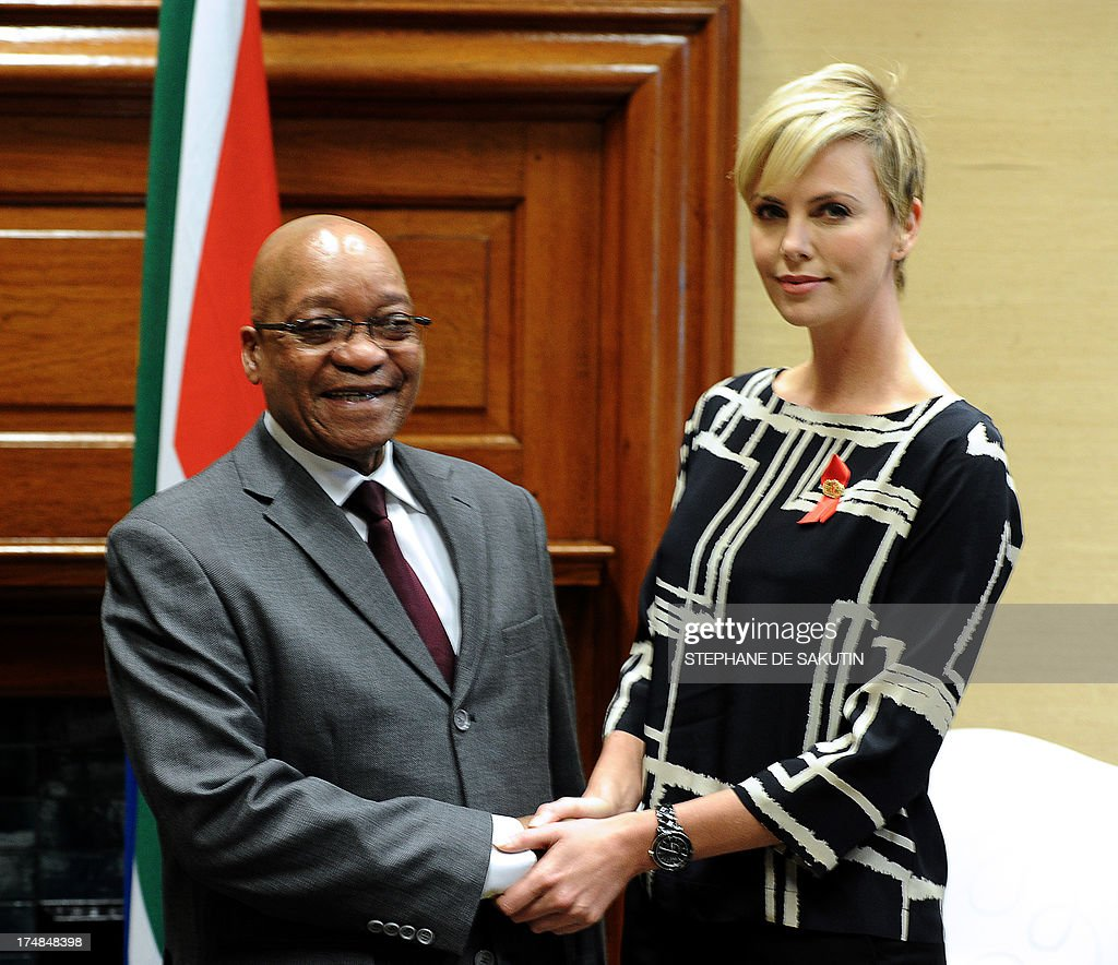 South African President Jacob Zuma shakes hands with South African-born Hollywood actress and UN Messenger of Peace, Charlize Theron, on July 29, 2013, at the Unions Building in Pretoria. Theron is accompanied by the Executive Director of UNAIDS Michel Sidibe to discuss the strides being made in the fight against HIV and AIDS and how collaboration can assist mitigate the pandemic's negative impact on young girls. They will also explore ways to support South Africa's efforts to enable young women and girls to lead healthier HIV and AIDS -free lives.