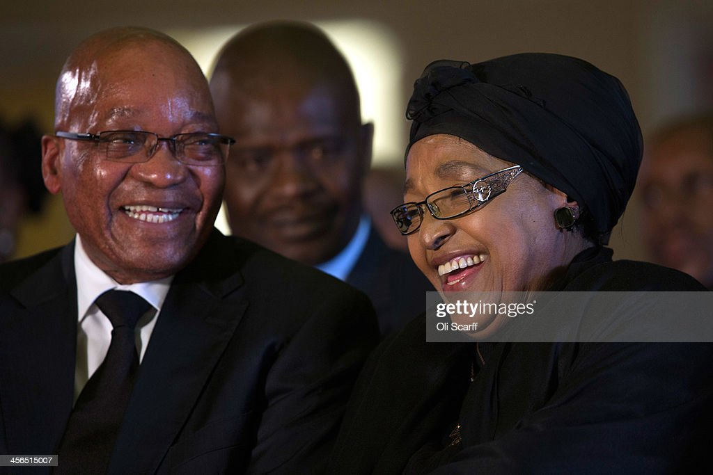 South African president <a gi-track='captionPersonalityLinkClicked' href=/galleries/search?phrase=Jacob+Zuma&family=editorial&specificpeople=564982 ng-click='$event.stopPropagation()'>Jacob Zuma</a> (L) shares a joke with with <a gi-track='captionPersonalityLinkClicked' href=/galleries/search?phrase=Winnie+Mandela&family=editorial&specificpeople=212886 ng-click='$event.stopPropagation()'>Winnie Mandela</a>, a former wife of Nelson Mandela, during an African National Congress (ANC) led alliance send off ceremony for former South African President Nelson Mandela at Waterkloof military airbase on December 14, 2013 in Pretoria, South Africa. The ANC held an official send off ceremony as the body of former South African President prepares to make one final journey to his hometown of Qunu for burial. Mr. Mandela passed away on the evening of December 5, 2013 at his home in Houghton at the age of 95. Mandela became South Africa's first black president in 1994 after spending 27 years in jail for his activism against apartheid in a racially-divided South Africa.