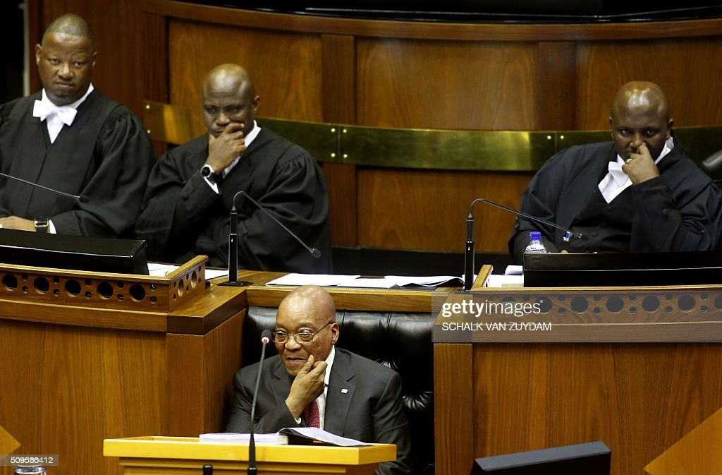 South African President Jacob Zuma sits down as he is interrupted trying to give his state of the nation address in Cape Town, South Africa on February 11, 2016. South Africa's radical leftist Economic Freedom Fighters (EFF) party walked out of President Jacob Zuma's state of the nation address after repeatedly interrupting his speech in chaotic parliamentary scenes. / AFP / POOL / Schalk van Zuydam