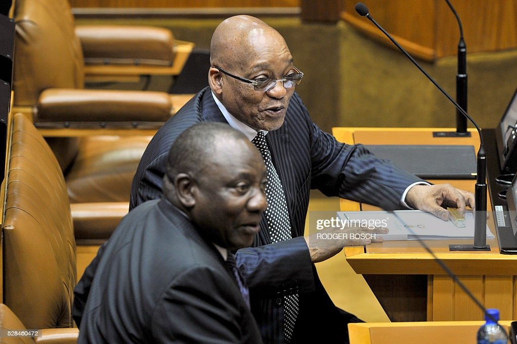 South African President, Jacob Zuma (R) speaks with Deputy President Cyril Ramaphosa, at the South African Parliament as most of the opposition parties were boycotted or suspended from the sitting, on May 5, 2016, in Cape Town. The day before, all the members of the opposition party of Economic Freedom Fights (EFF), were manhandled out of the chamber for disrupting a debate on the budget. / AFP / RODGER
