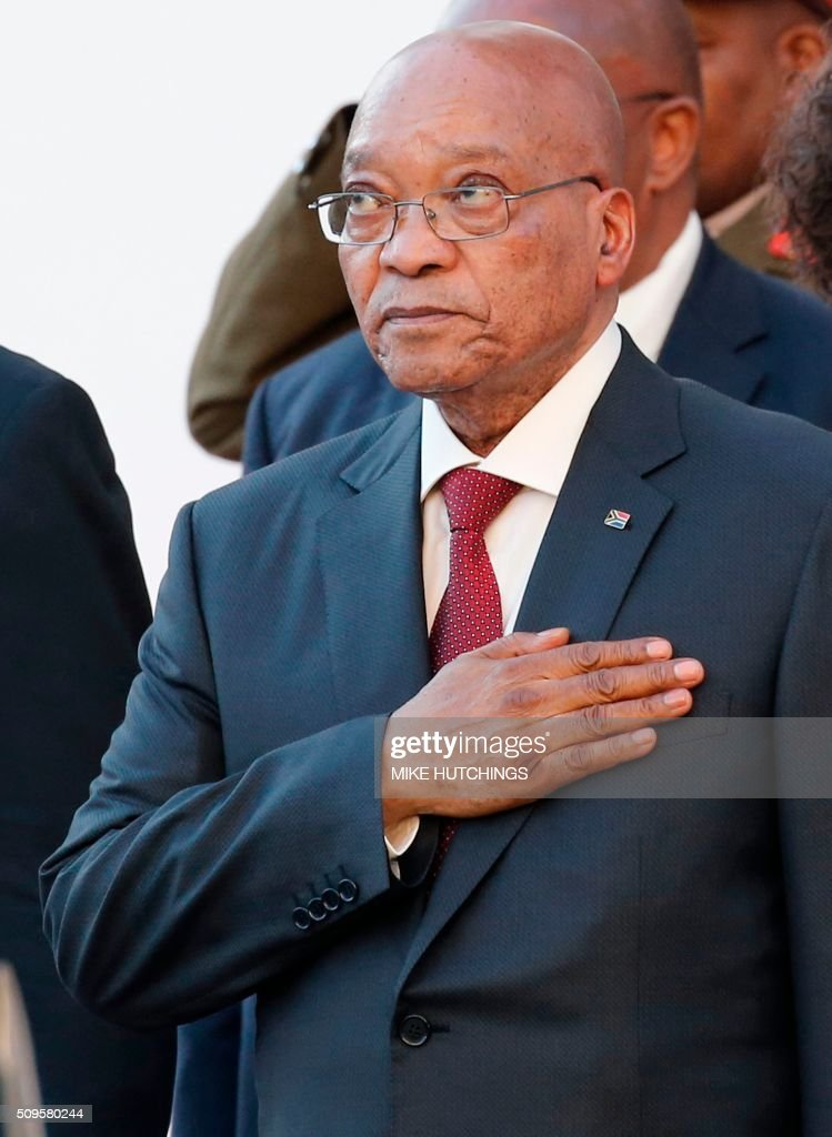 South African president Jacob Zuma stands for the National Anthem as he arrives for the State of the Nation Address on February 11, 2016 in Cape Town. South African President Jacob Zuma delivers his annual state of the nation address on February 11, 2016 as frustration grows over his leadership and the country's lack of progress since apartheid ended more than 20 years ago. Zuma's critics accuse him of allowing a small black elite to enrich itself, failing to help the poor, and overseeing national economic decline as South Africa struggles to overcome the legacy of decades of white-minority rule. / AFP / POOL / Mike HUTCHINGS