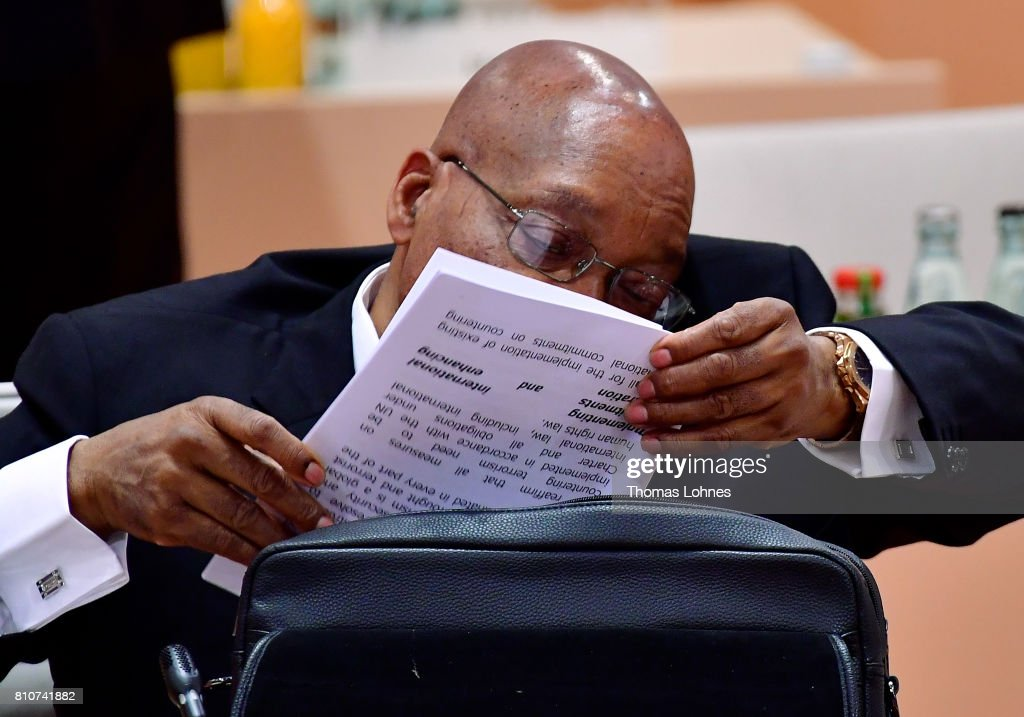 South African President Jacob Zuma talks on a mobile phone while at the same time looking through documents from his briefcase at the morning working session on the second day of the G20 economic summit on July 8, 2017 in Hamburg, Germany. G20 leaders have reportedly agreed on trade policy for their summit statement but disagree over climate change policy.