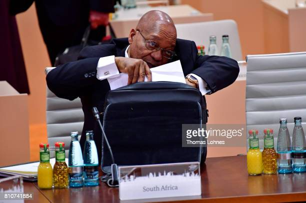 South African President Jacob Zuma talks on a mobile phone while at the same time looking through documents from his briefcase at the morning working...