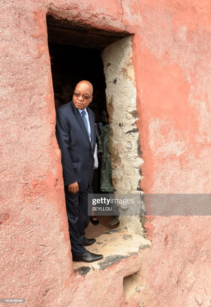 South African President Jacob Zuma visits looks out of the 'door of no return' during a tour of Goree Island, off Dakar, on October 2, 2013. The island of Goree, four kms (about two miles) off Dakar, processed many of the estimated 12 million Africans who over three centuries crossed the Atlantic Ocean bound in chains, their lives and liberty traded in the US slave market.