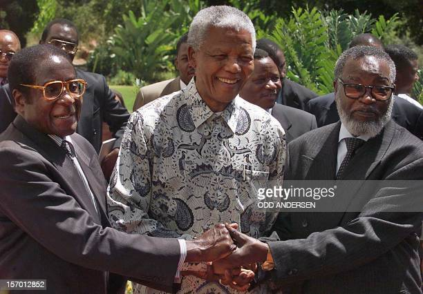 South African President Nelson Mandela and his counterparts Zimbabwean President Robert Mugabe and Namibia's Sam Nujoma shake hands after a joint...