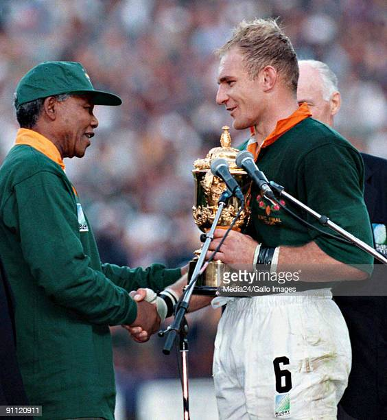 South African president Nelson Mandela dressed in a No 6 Springbok jersey congratulates the Springbok captain Francois Pienaar after South Africa...